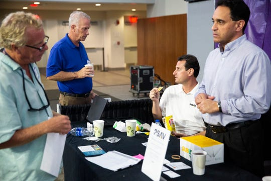Two job seekers, Steve Eisenberg, left, and Grief Herriman, second left, talks to two recruiters for PSAV during a job fair at the Suncoast Credit Union Arena on Thursday, October 17, 2019, in Fort Myers.
