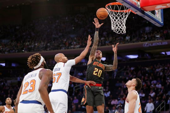Atlanta Hawks forward John Collins (20) shoots with New York Knicks center Mitchell Robinson (23) and forward Taj Gibson (67) defending during the first half of a preseason NBA basketball game in New York, Wednesday, Oct. 16, 2019. (AP Photo/Kathy Willens)