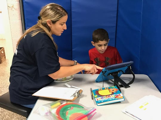 Teacher Lisa Ficocello helps 8-year-old Mason identify objects through use of his iPad at Nothern Valley Central, the Valley Program's permanent home in Norwood.