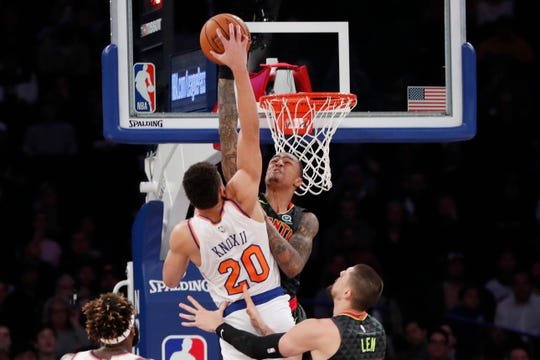 Atlanta Hawks forward John Collins, rear, defends against New York Knicks forward Kevin Knox (20) during the first half of a preseason NBA basketball game in New York, Wednesday, Oct. 16, 2019.