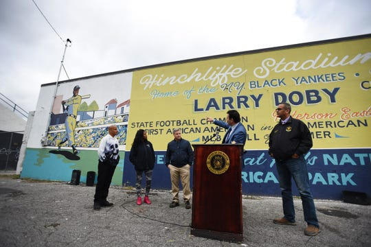 (L to R) David Thompson, Founder and Program Director of Halls That Inspire, Rhonda Sujai, Designer & Artist of Halls That Inspire, Kyle Hughes, Paterson Firefighter and Commissioner on Paterson Art Commission and Louis Velez, Fifth Ward Councilman, listen as Mayor Andre Sayegh talks to the media as he unveils the new Larry Doby mural at Hinchliffe Stadium in Paterson on 10/17/19.