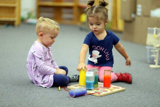 From left, Brynlee Keeler and Caia Saludares are entertained at Play Sharity Museum and Lending Library.