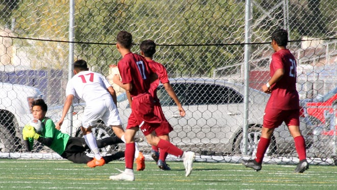 """Sophomore Wildcat goal keeper Alejandro """"Big Boy"""" Chavez (green jersey) makes a diving save during Wednesday's 4-0 Deming High loss to the visiting Gadsden High Panthers."""