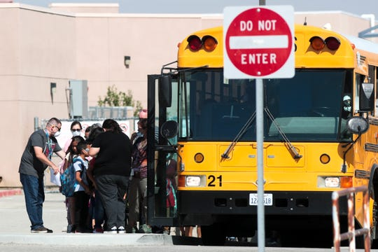 Faculty members help students board the bus at Las Palmitas Elementary School on Thursday, October 17, 2019 in Thermal, Calif. after a dump fire caused the school to shut down.