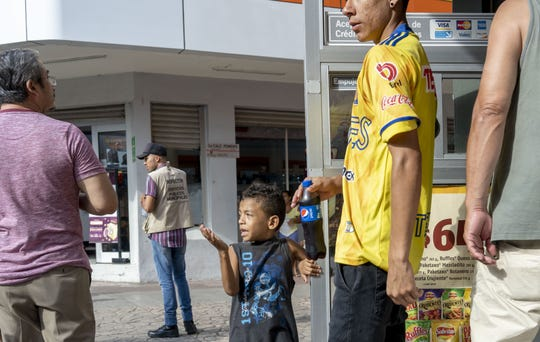 Oscar Rodriguez, 8,  from Honduras, begs for money in Tapachula, Mexico, in summer 2018.