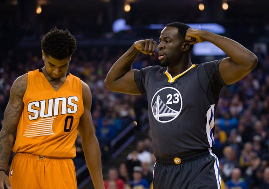 Golden State Warriors forward Draymond Green (23) flexes his muscles ahead of Phoenix Suns forward Marquese Chriss (0) after a basket and a  foul during the first quarter at Oracle Arena in a 2016 game.