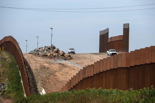Camionetas se mueven en la sección de la cerca fronteriza en Tijuana, B.C.
