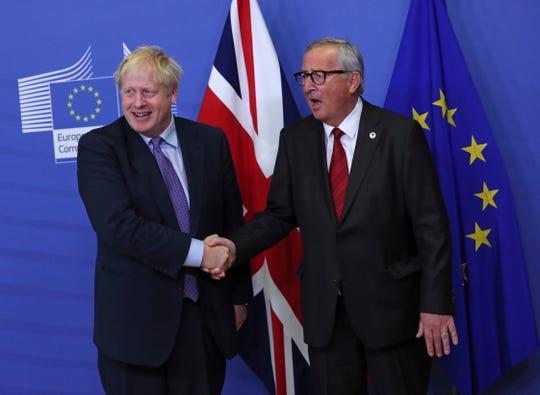 El primer ministro de Gran Bretaña Boris Johnson (izq.) estrecha la mano con el el presidente de la comisión europea Jean-Claude Juncker.
