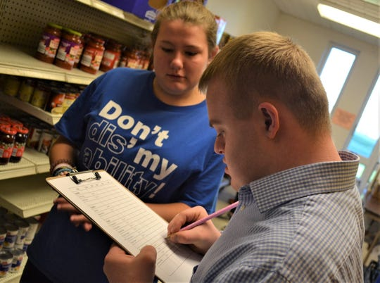 Woodmore sophomore Baize Kaylor writes down amounts on the food tally sheet as Raina Yerg looks on. The class will use those totals to determine what food needs to be purchased to keep the pantry stocked.