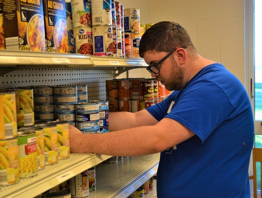 Woodmore senior Aidan Treat organizes cans at the Elmore Food Pantry.