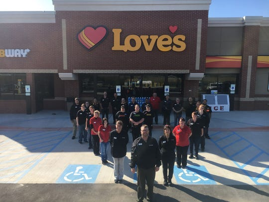 Love's Travel Stop & Country Store General Manager Travis Smith stands at the point of the heart with other employees at the newly opened location in St. Clair Township on Oct. 10, 2019.