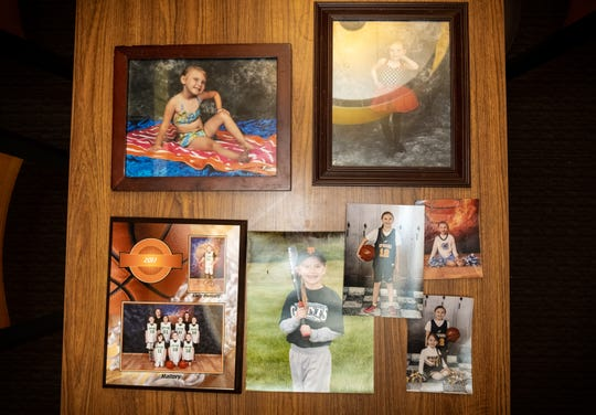 Sports photos of Mallory Milhoan are arranged on a table. Throughout her childhood Mallory participated in different sports, including basketball, baseball, cheer and cross country.