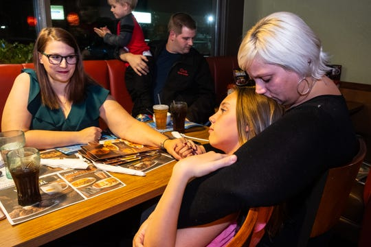 Malinda Evans, right, holds hands with her friend Robin Mattox-Burge, left, while her daughter Mallory Milhoan, 12, leans against her Wednesday, Oct. 16, 2019, at Denny's in Fort Gratiot. Mallory was diagnosed with severe scoliosis in late 2016. A masquerade ball is being held at Cros-Lex High School Nov. 2 to raise funds for her medical treatments.