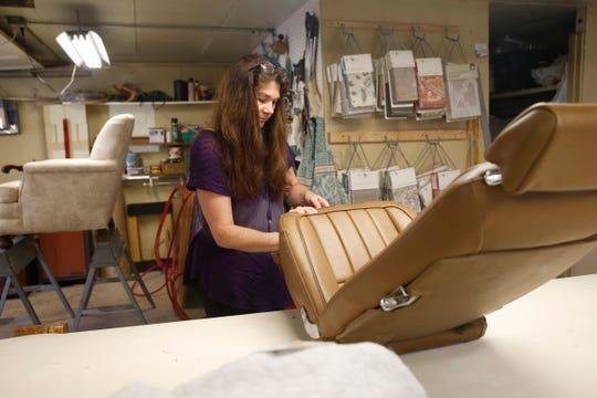 Deborah Loos, owner of Deb's Slipcovers and Upholstery, makes some final adjustments to a recently reupholstered Corvette seat at her shop on October 10, 2019.