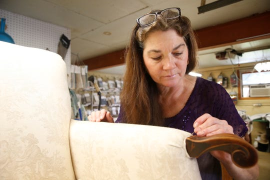 Deborah Loos, owner of Deb's Slipcovers and Upholstery, puts the finishing touches on an antique chair she recently re-upholstered on October 10, 2019.