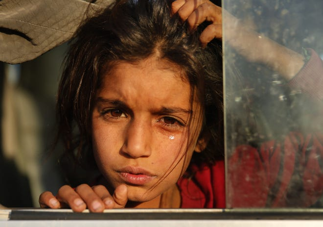 A Syrian girl who is newly displaced by the Turkish military operation in northeastern Syria, weeps as she sits in a bus upon her arrival at the Bardarash camp, north of Mosul, Iraq, Wednesday, Oct. 16, 2019. The camp used to host Iraqis displaced from Mosul during the fight against the Islamic State group and was closed two years ago. The U.N. says more around 160,000 Syrians have been displaced since the Turkish operation started last week, most of them internally in Syria.
