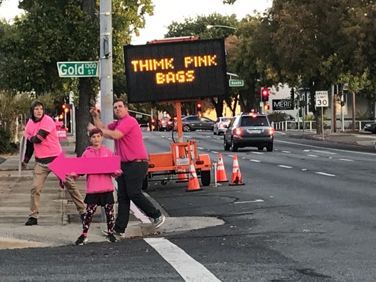 Think Pink volunteers point traffic to the bag giveaway at Tri Counties Bank on South Street in downtown Redding on Thursday, Oct. 17, 2019.