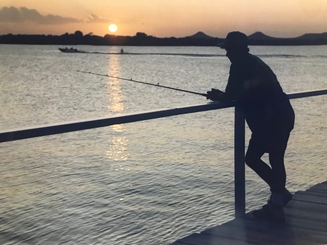Israel Pena leans on the rail at the pier on Lake Nasworthy while fishing at sundown in August of 1992.