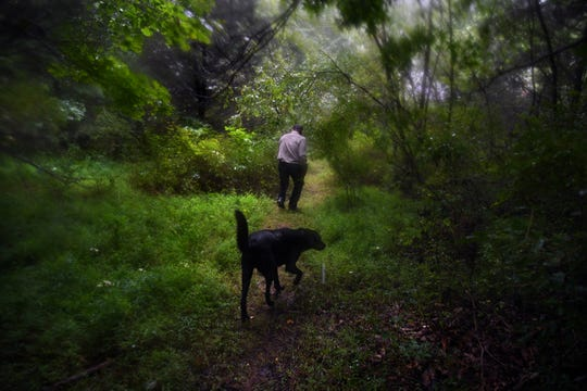Drew Miller walks the heavily wooded Fortitude Ranch grounds followed by a guard dog.