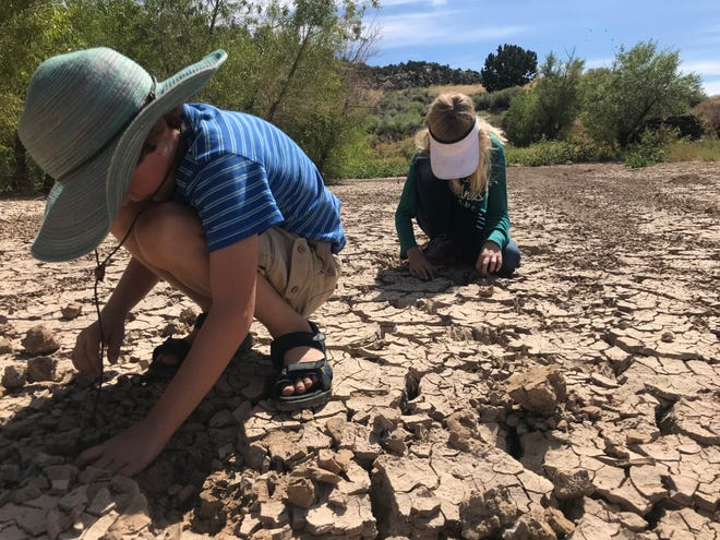 Children play in the dried clay near Sand Cove Reservoir in Washington County on Sept. 22, 2019.