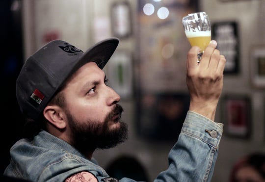Daniel Vego of Hijos de la Guayaba Taproom inspects a beer at his Juarez bar Wednesday.