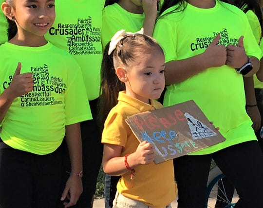 """A girl holds a sign stating """"Please keep us safe"""" at the launch of a pedestrian safety campaign at O'Shea Keleher Elementary in El Paso on Thursday."""