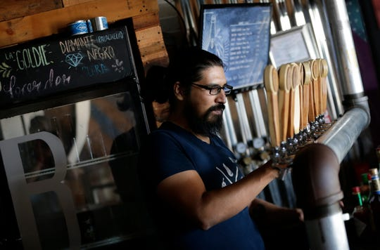 Bartender Sergio Martinez serves eight craft brewed beers at Border Brewing Company in Juarez. The craft beer scene in Juarez is in its infancy but some brewers are already distributing their creations to bars and stores.