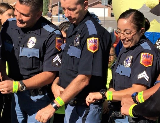 El Paso police officers show off reflective slap wristbands being given to children at police stations in a pedestrian safety campaign.