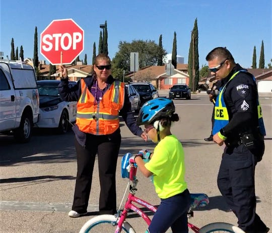 A girl walks a bicycle during a crosswalk safety demonstration Thursday at O'Shea Keleher Elementary School in far East El Paso.