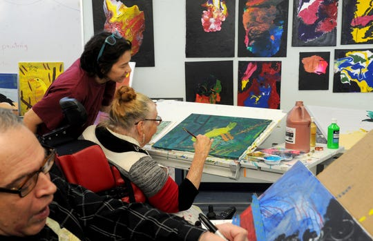 Don Geagan, left,  paints as Veronica De Jesus, middle, head art facilitator, helps Judy Lalley with her art project inside the adult day program at Conejo Valley Adult School. The day program is being closed by United Cerebral Palsy of Los Angeles, Ventura and Santa Barbara Counties.