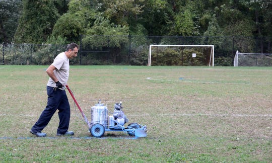 John Lagani, a custodian with the Rye City School District, repaints the fading lines on the grass athletic field at Nursery Field in Rye, Oct. 17, 2019.