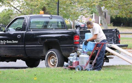 John Lagani, a custodian with the Rye City School District, refills his paint sprayer, as he repaints the fading lines on the grass athletic field at Nursery Field in Rye, Oct. 17, 2019.