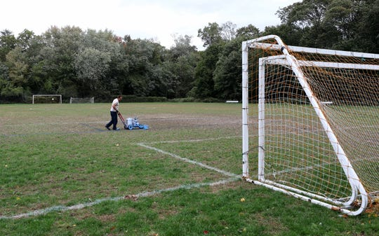 John Lagani, a custodian with the Rye City School District, repaints the fading lines on the grass athletic field at Nursery Field in Rye, Oct. 17, 2019. The field could become a turf playing surface later this year.