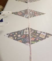 Open the triangles of fabric up, right sides facing down. Place the ribbon or twine right against the fold crease.
