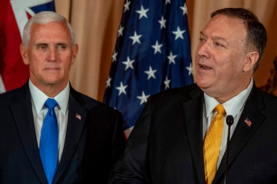 Secretary of State Mike Pompeo, right, gives a speech as Vice President Mike Pence looks on during a luncheon at the State Department in Washington, D.C., on Sept. 20, 2019.