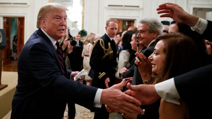 President Donald Trump reaches to shake hands during a reception for Italian President Sergio Mattarella in the East Room of the White House.