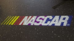 The NASCAR logo on the floor in NASCAR's Fan and Media Engagement Center during a race at Bristol.