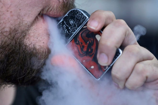 A man uses an electronic cigarette exhales in Mayfield Heights, Ohio on Oct. 4, 2019. A Montana judge has signed a temporary restraining order that prohibits a temporary ban enacted by Gov. Steve Bullock on flavored vaping products in Montana that was to take effect Tuesday.