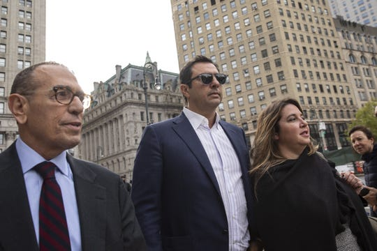 Andrey Kukushkin (center) leaves a hearing Manhattan federal court arraignment in New York City on October 17, 2019, with defense attorneys Gerald Lefcort, (left) and Faith Friedman (right).