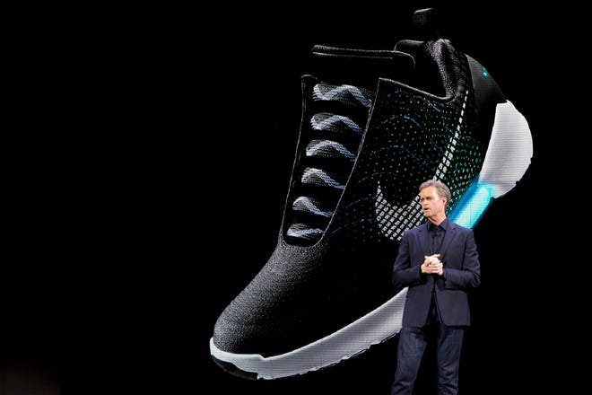 An image of the Nike HyperAdapt 1.0 is projected on a screen as Nike CEO Mark Parker speaks during a news conference, Wednesday, March 16, 2016, in New York. (AP Photo/Mary Altaffer) ORG XMIT: NYMA101