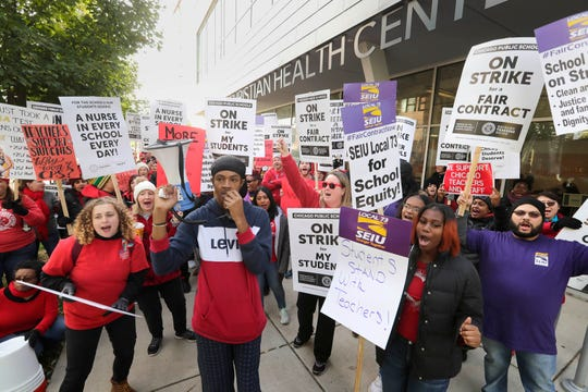 Kaleb Autman, a supporter of the strike leads lecturers and SEIU supporters  at Breakthrogh, a non-profit for these tormented by poverty, where Chicago Mayor Lori Lightfoot learn a e book to younger of us.