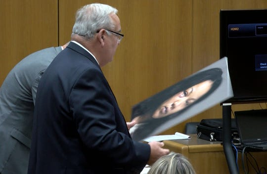 Defense attorney Alton Kenney holds Ciara Williams' booking photo during a hearing in State Superior Court in Toms River Friday, October 18, 2019.  She is charged with the murder of her fiancee in Brick Township.