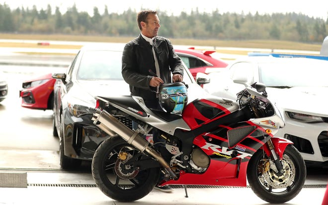 Circuit of the Northwest's Brian Nilsen gets ready to don his motorcycle helmet for his grand entrance on the bike behind the sports cars on display at the Bremerton National Airport inside the Avian Flight Center hangar on Friday.