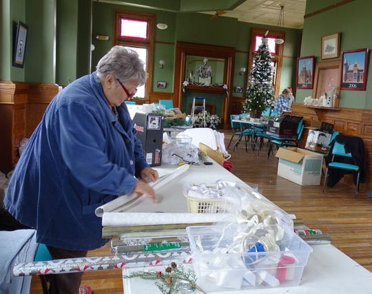 Sue Streib wraps boxes as members of the Bucyrus Preservation Society decorate the Toledo and Ohio Central Train Depot on Thursday.