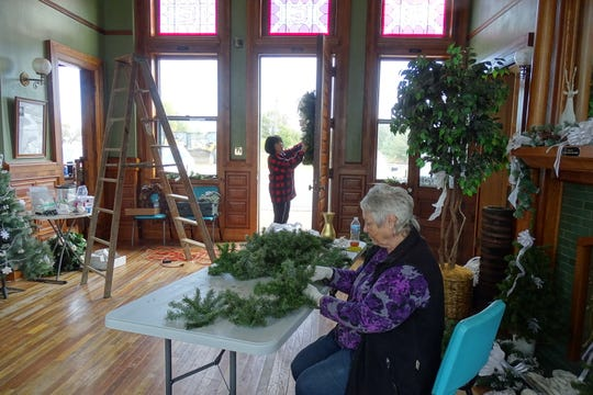 Mary Lee Minor decorates a wreath on the door and Carolyn Kelley arranges garlands as members of the Bucyrus Preservation Society decorate the Toledo and Ohio Central Train Depot on Thursday.