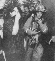 Green Township Fire Department Lt. Scott Souders and Oak Hills High School student Jennifer Reitz, then 17, wait outside the school auditorium after mace was sprayed into the crowd on April 23, 1998.