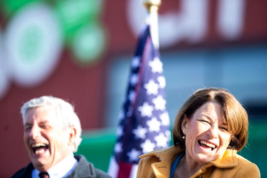 "Democratic presidential candidate U.S. Sen. Amy Klobuchar of Minnesota laughs during the kickoff event at her ""For All of America"" bus tour along with state Rep. Andy McKean, a lifelong Republican who switched party affiliation this year. They were outside the NewBo City Market in Cedar Rapids on Oct. 18."