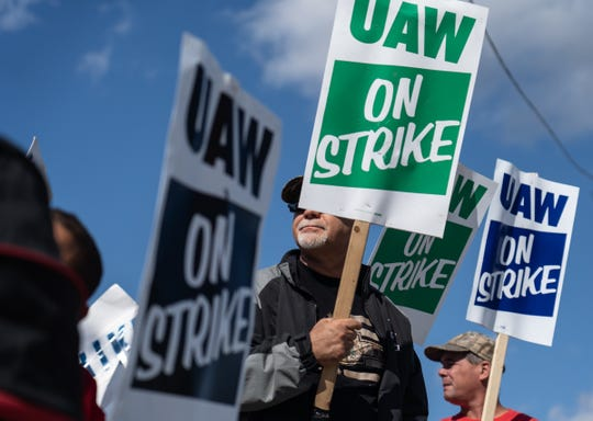 UAW members stand on the picket line outside of the north gate of General Motors Flint Assembly on Monday, October 7, 2019 as they remain on strike from General Motors.