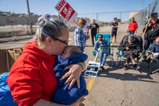 General Motors Flint Assembly temporary worker Adrienne Schultz kisses her 2-month-old son Tommy Gippert while standing on the picket line at the north gate of General Motors Flint Assembly on Monday, October 7, 2019. Schultz brings the infant with her on the line each week and often has co-workers getting to see the baby for the first time since his birth.