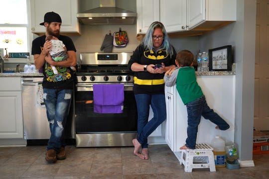 "General Motors Flint Assembly temporary worker Adrienne Schultz checks her phone while in the kitchen of her home in Davison on Tuesday, October 8, 2019 with her fiance, Dean Gippert, their 2-month old son Tommy Gippert and son Ansen Schultz. ""I think the first initial push of it is starting to wear off,"" Schultz said about the strike against General Motors. ""It's a little stressful. It's a huge shift from being in the plant 60 hours a week."""
